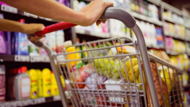 A female pushing a shopping cart down a grocery store aisle