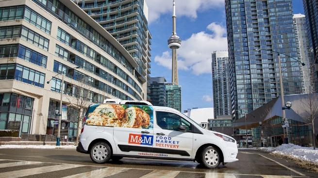 M&M delivery van against the Toronto cityscape