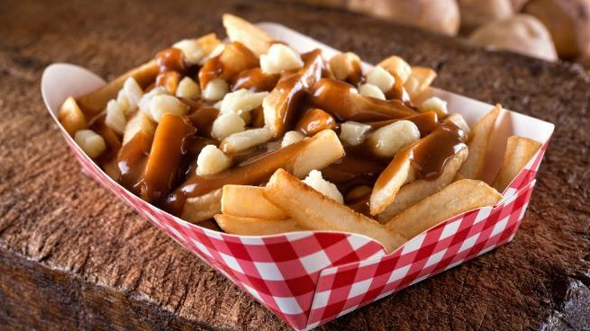 A serving of delicious poutine with french fries, cheese curds and gravy on a rustic wooden board