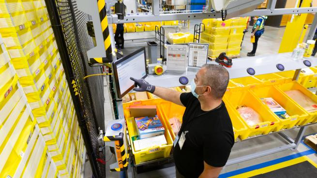 An Amazon employee wearing a face mask and filling orders