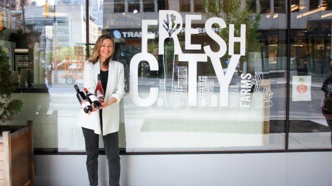 Head sommelier Jennifer Huether standing outside Fresh City holding a bottle of wine