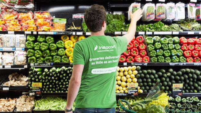 An Instacart shopper picking products from the produce section in a grocery store