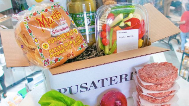 A cardboard Pusateri's box filled with grocery items including hamburger buns
