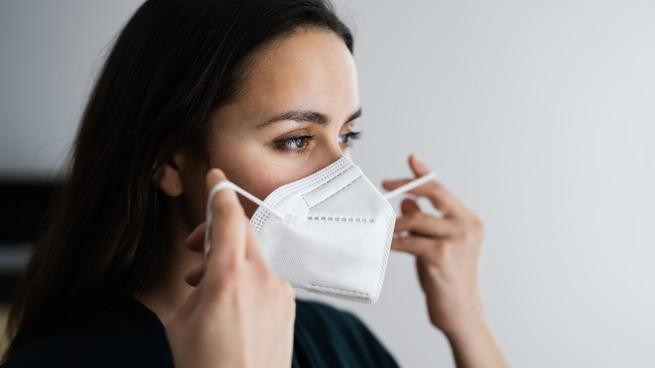 A woman putting on an N-95 mask