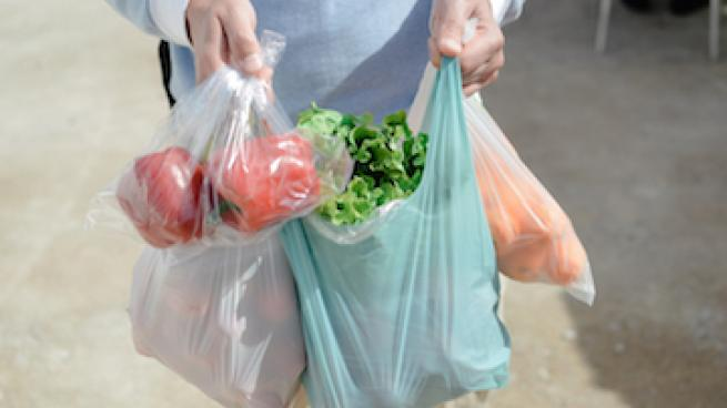 Person carrying plastic bags filled with groceries