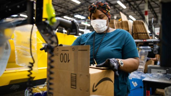An Amazon employee packs a box in a warehouse while wearing a mask