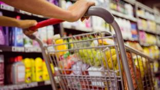 Female shopper pushing a cart filled with groceries down an aisle